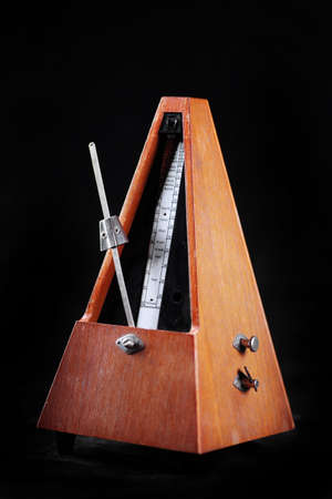 Vertical shot of a vintage metronome, on black photo