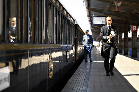 Bucharest, Romania - September 3, 2012: A man in uniform walks by the Orient Express train, shortly after arriving in Bucharest. The Venice Simplon-Orient-Express, is a private luxury train service, known as the Orient Express.
