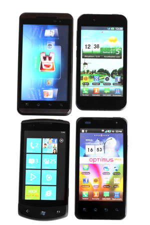 Bucharest, Romania - October 29, 2012: Four smartphones isolated on white, using various operating systems, like Windows Mobile or Android. Smartphones are mobile phones using advanced computing capability and connectivity.