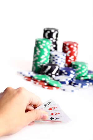 Hand holding four aces during poker game, with piles of chips in the background. photo