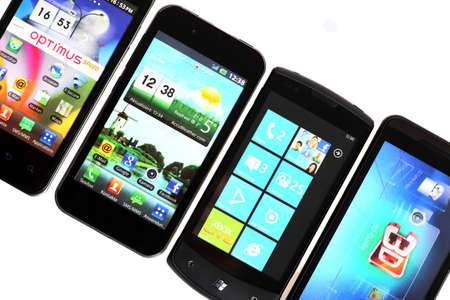 Bucharest, Romania - October 29, 2012: Four smartphones displayed in line, isolated on white, using various operating systems, like Windows Mobile or Android. Smartphones are mobile phones using advanced computing capability and connectivity. Stock Photo - 16870305