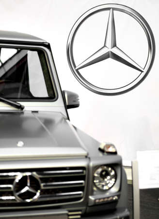 daimler: Bucharest, Romania - October 22, 2012: Mercedes logo is displayed next to a car in Bucharest. Mercedes-Benz is a multinational division of the German manufacturer Daimler AG, that produces automobiles, buses, coaches, and trucks. Editorial