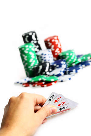 Hand holding four aces during poker game, with piles of chips in the background  Stock Photo - 17241318