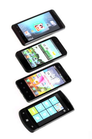 advanced computing: Bucharest, Romania - October 29, 2012: Four smartphones displayed in line, isolated on white, using various operating systems, like Windows Mobile or Android. Smartphones are mobile phones using advanced computing capability and connectivity.