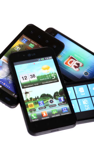 advanced computing: Bucharest, Romania - October 29, 2012: Four smartphones isolated on white, using various operating systems, like Windows Mobile or Android. Smartphones are mobile phones using advanced computing capability and connectivity. Editorial