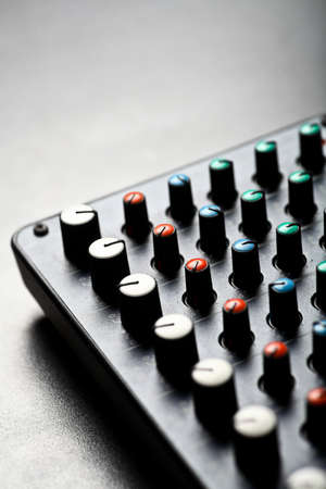 Detail of a music mixer desk with various knobs photo