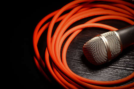 One shiny microphone and a rolled up red wire