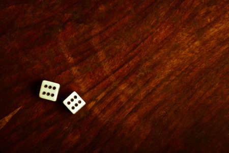 Two dice displaying six on a vintage wood plank photo