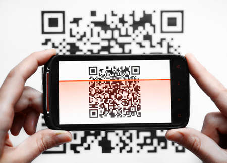 Two hands holding a mobile phone scanning a QR code Stock Photo - 19664984