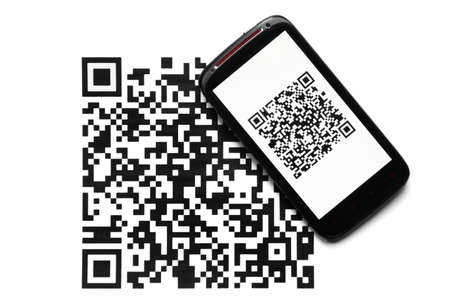 A mobile phone next to a QR code printed on paper Stock Photo - 19664980