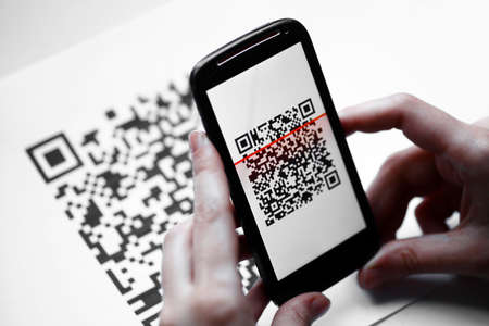 bar code reader: Two hands holding a mobile phone scanning a QR code