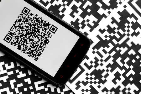 A mobile phone next to some QR codes printed on paper photo