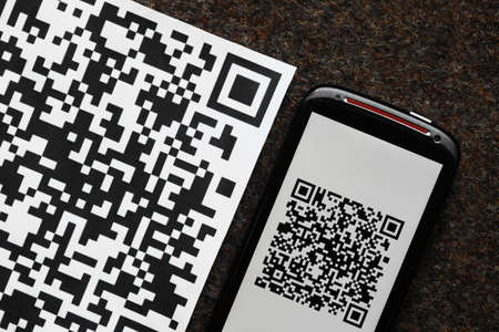 A mobile phone next to a QR code printed on paper Stock Photo - 19828873