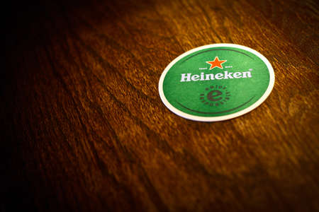 Bucharest, Romania - May 2, 2013: Color shot of a Heineken beer pad on a wooden surface. Heineken is a Dutch beer brewed by Heineken International. Stock Photo - 19769169