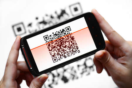 Two hands holding a mobile phone scanning a QR code photo