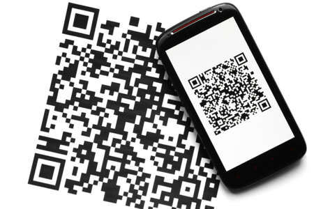 A mobile phone next to a QR code printed on paper photo
