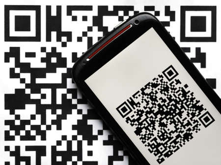 A mobile phone next to a QR code printed on paper Stock Photo - 20259434
