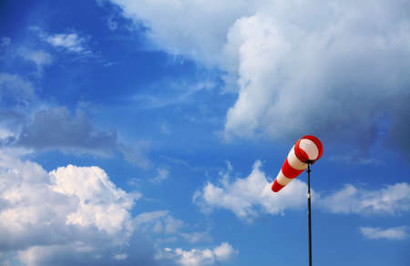 weather gauge: A red wind vane against a blue cloudy sky