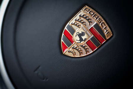 bucharest: Bucharest, Romania - June 13, 2013: Detail on the logo of a Porsche car on the steering wheel. Porsche is a German automobile producer, headquartered in Zuffenhausen, Stuttgart. Editorial