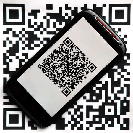 A mobile phone next to a QR code printed on paper Stock Photo - 20412139