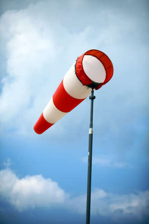 meteorological: A red wind vane against a blue cloudy sky