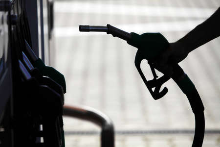 octane: Detail of a hand holding a fuel pump at a station