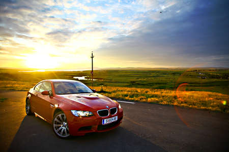 Boekarest, Roemenië - 3 juli 2013: Een BMW M3 auto rijdt door een prachtig landschap, bij zonsondergang. De BMW M3 is een high-performance versie van de BMW 3-serie, ontwikkeld door BMW motorsport divisie, BMW M. Redactioneel