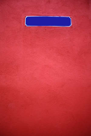 Color shot of an empty blue street sign on a red wall photo