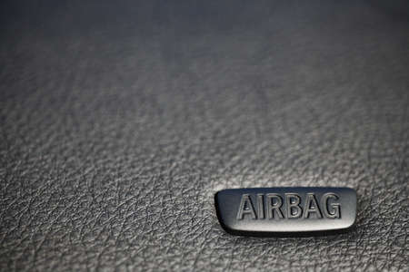 The word 'Airbag' is written on a car's dashboard photo