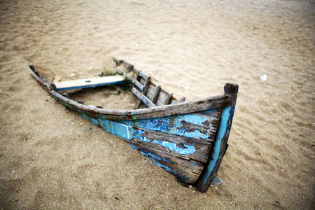 Color picture of an abandoned boat stuck in sand Imagens
