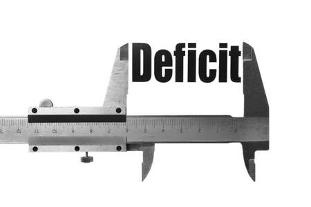 Close up shot of a caliper measuring the word 'Deficit' photo