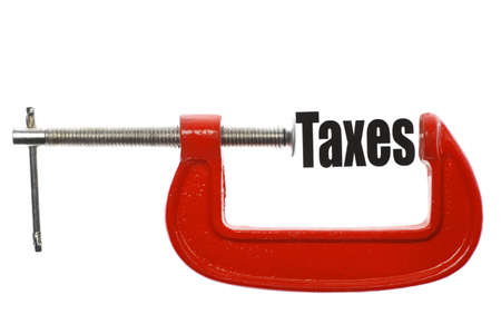 The word Taxes is compressed with a vice. Business metaphor. photo