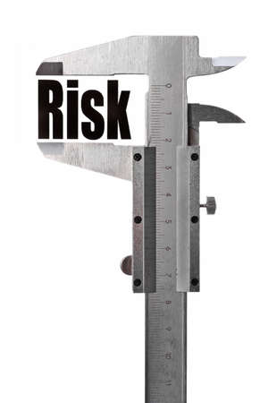 Close up shot of a caliper measuring the word  Risk  photo