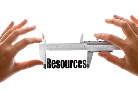 Two hands holding a caliper, measuring the word Resources. photo
