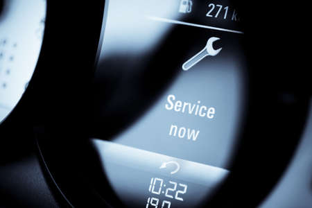 service: Detail with a warning icon on the dashboard of a car reading Service Now.