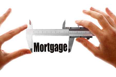 Two hands holding a caliper, measuring the word Mortgage. photo