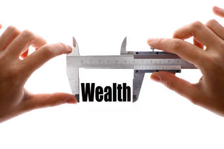 Close up shot of a caliper measuring the word Wealth photo