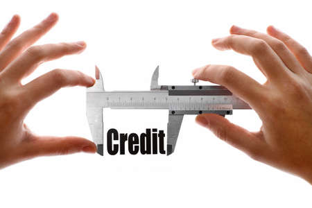 deficit: Close up shot of a caliper measuring the word Credit