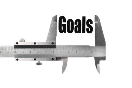 Close up shot of a caliper measuring the word 'Goals' photo