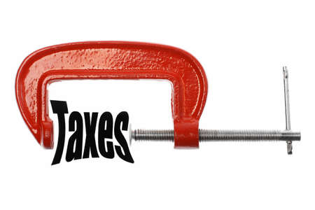 The word 'Taxes' is compressed with a vice. Business metaphor. photo