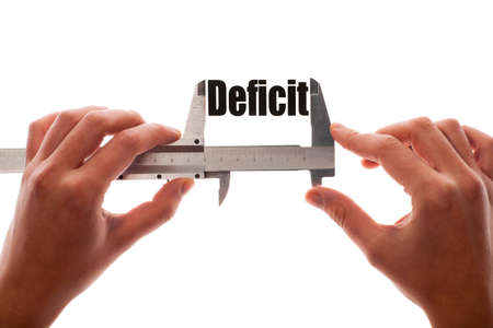 deficit: Close up shot of two hands holding a caliper measuring the word Deficit
