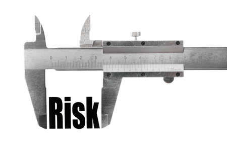 Close up shot of a caliper measuring the word Risk