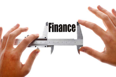 Close up shot of two hands holding a caliper and measuring the word Finance Stock Photo