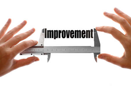 Two hands holding a caliper, measuring the word 'Improvement'. photo