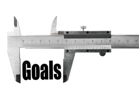 Close up shot of a caliper measuring the word Goals Stock Photo