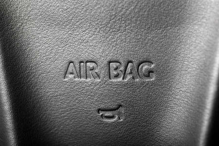 The word 'Airbag' is written on a car's steering wheel photo