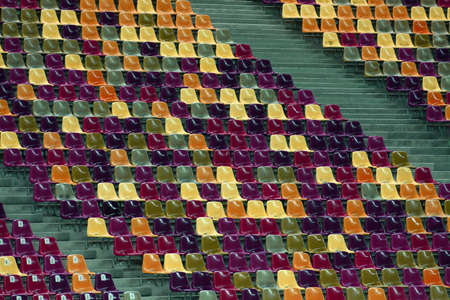 theater audience: Rows of empty seats of different colors in a stadium