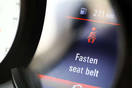 Detail with the dashboard of a car displaying a Fasten Seat Belt message. Imagens