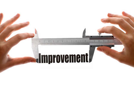 performance improvement: Two hands holding a caliper, measuring the word Improvement. Stock Photo