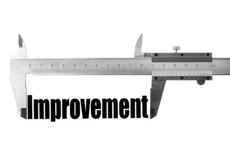 Shot of a caliper, measuring the word 'Improvement'. photo